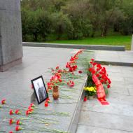 Rudé květy jako symboly prolité krve Čechoslováků a Sovětů v boji proti fašismu. Na fotografii brigádní generál Svoboda, velitel 1. československého armádního sboru.